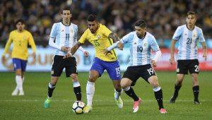Paulinho, volante da Seleção Brasileira, fugindo da marcação dos jogadores argentinos